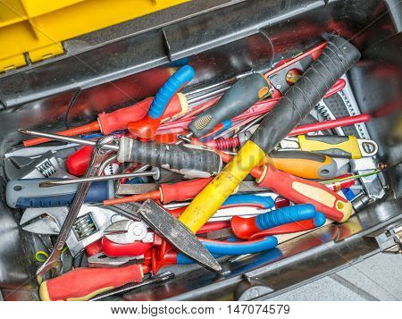 Plastic toolbox full of hand tools shot from above