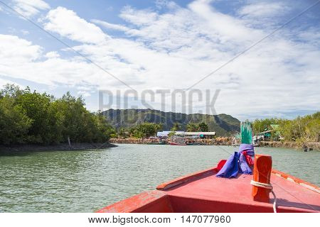 long tail fishing boat floating in a riverside country