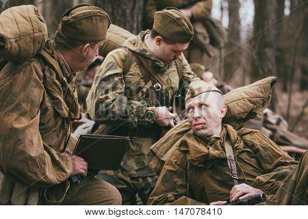 Pribor, Belarus - April 04, 2015: Group of unidentified re-enactors dressed as Soviet soldiers in overcoat resting in forest