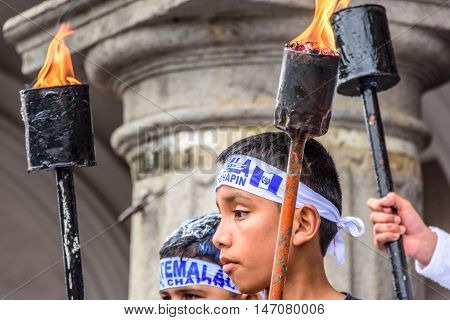 Antigua Guatemala - September 14 2015: Patriotic boys hold lit torches outside city hall during Guatemalan Independence Day celebrations