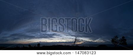 Small island in the Baltic Sea panorama. Single dead tree sunset and stormy night on the beach. Mohni Estonia Europe.