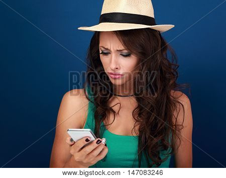Angry Woman In Hat Looking And Reading Sms On Mobile Phone In Stress Emotion On Blue Background. Clo