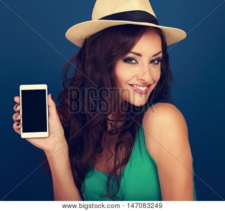 Happy Smiling Woman In Hat Holding In Hand And Showing Modern Mobile Phone On Blue Background. Close