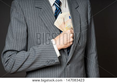Businessman in suit putting banknotes in his jacket breast pocket. Business man is holding cash stack of fifty euros money. Person pays in euro bills isolated gray background.