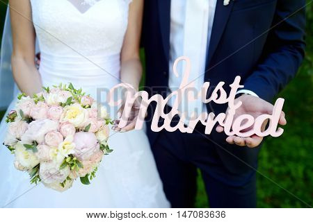 Wedding inscription JUST MARRIED on the nature. Cute couple is holding hands. Beauty bride with groom. Beautiful model girl in white dress. Man in suit. Female and male portrait. Close-up arms