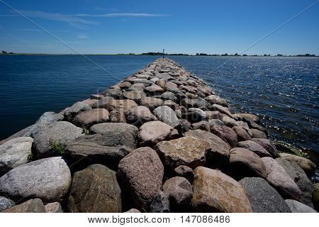 Embedded stones. Rocky beach peaceful sea harbor. Mole in Munalaid Estonia. Baltic sea Europe
