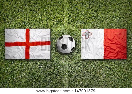 England and Malta flags on a green soccer field, 3D illustration
