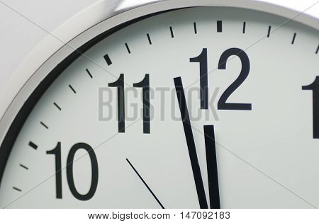 Analog clock that is close to 12:00 o'clock
