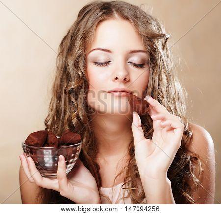 Beautiful curly woman eating a chocolate bonbon
