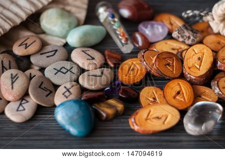 wooden, rune stone with his own hands among the crystals on a dark background