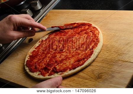 Hand Spreading Tomato Puree On Pizza Base