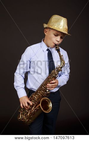 child playing the saxophone. young jazzman in a shiny hat, shirt and tie enthusiastically playing the saxophone