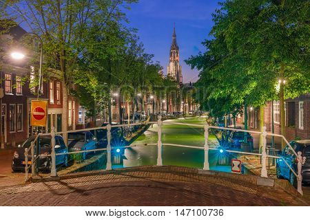 Night Oosteinde canal and Gothic Protestant Nieuwe Kerk, New church in Delft, Holland, Netherlands