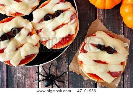 Halloween Mummy Mini Pizzas Overhead Scene On Rustic Wooden Background