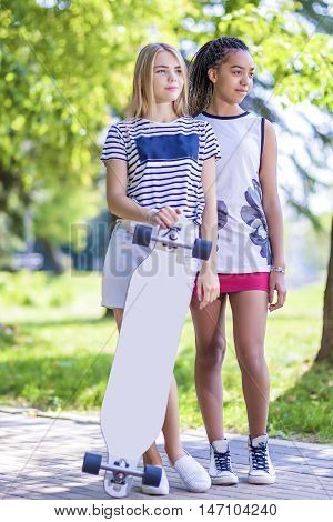 Teenager Concepts. Two Teenage Girlfriends Together With Longboard Outdoors in Park. Vertical Image