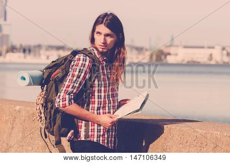 Man hiker backpacker with backpack by seaside reading map searching looking for direction guide. Adventure tourism active lifestyle. Young long haired guy tramping