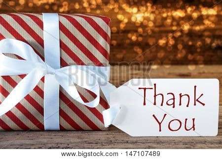 Macro Of Christmas Gift Or Present On Atmospheric Wooden Background. Card For Seasons Greetings, Best Wishes Or Congratulations. White Ribbon With Bow. English Text Thank You