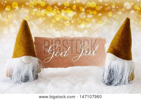 Christmas Greeting Card With Two Golden Gnomes. Sparkling Bokeh And Noble Background With Snow. Swedish Text God Jul Means Merry Christmas