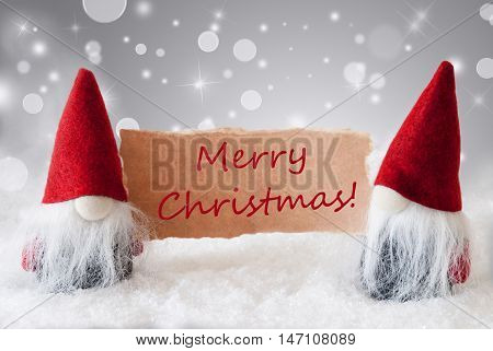 Christmas Greeting Card With Two Red Gnomes. Sparkling Bokeh And Noble Silver Background With Snow. English Text Merry Christmas