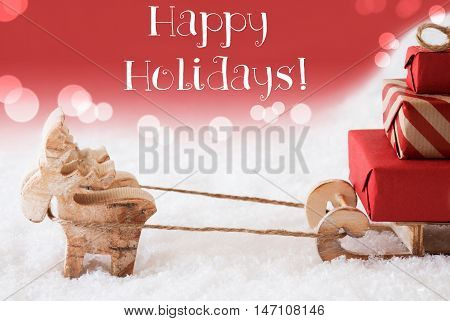 Moose Is Drawing A Sled With Red Gifts Or Presents In Snow. Christmas Card For Seasons Greetings. Red Christmassy Background With Bokeh Effect. English Text Happy Holidays