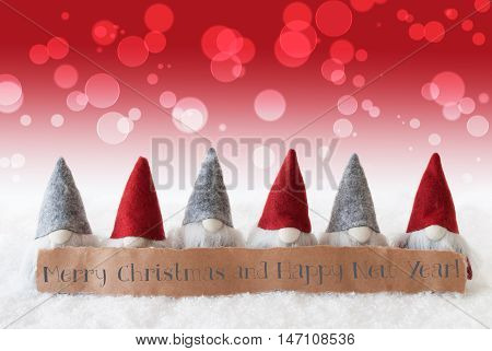 Label With English Text Merry Christmas And Happy New Year. Christmas Greeting Card With Red Gnomes. Bokeh And Christmassy Background With Snow.