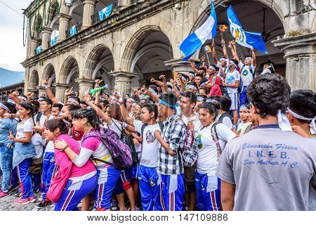 Antigua Guatemala - September 14 2015: Students wave Guatemalan flags & lit torches & pose for photos outside city hall during Guatemalan Independence Day celebrations
