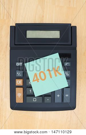 Black calculator with a display on a desk with green sticky note with text 401K