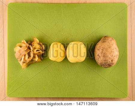 Two unpeeled and one peeled potatoes with skinsin center of green plastic board, simple food preparation illustration, vegetarian dieting, top view still life with bottom copyspace