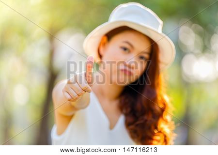 Asian woman showing thumbs-up with focus on hand on parking background