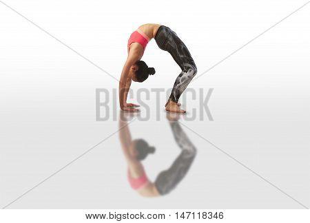 Woman doing yoga kapotasana on white background