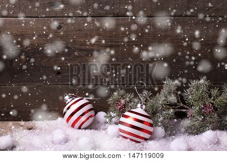 Christmas balls and branches fur tree on aged wooden background. Drawn snow. Decorative christmas composition. Selective focus. Place for text.