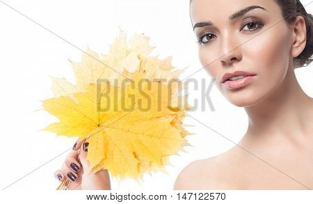 beauty portrait of attractive caucasian young woman brunette isolated on white studio shot face skin makeup looking at camera hand holding yellow marple autumn leave
