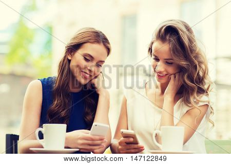 technology, lifestyle, friendship and people concept - happy young women or teenage girls with smartphones and coffee cups at cafe outdoors