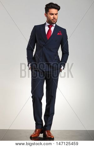 arrogant elegant man in double breasted suit standing with hands in pockets and looks to side on grey studio background