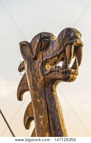 The wooden figure of a dragon's head on the prow of an ancient ship.