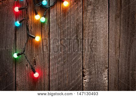 Christmas colorful lights on wooden table with copy space