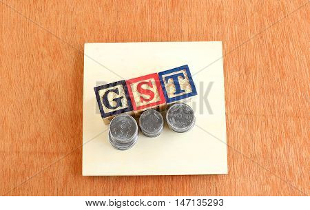 Indian goods and services tax (GST) concept highlighted through wooden blocks with letters G, S and T and stacks of Indian currency coins.