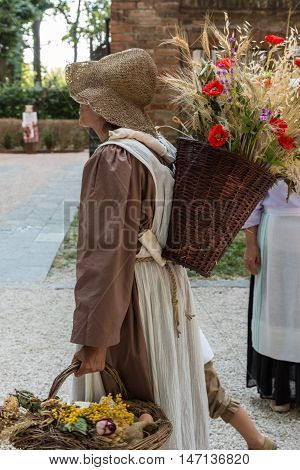 Wicker Basket Filled with Sheafs of wheat and Red Flowers Carried over the Shoulder of Young Countrywoman