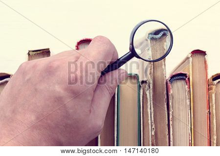 Magnifying glass in hand against the background of standing in a row of old books / search of necessary information