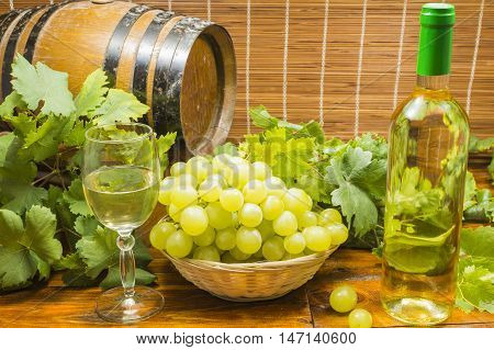 bottle of white wine, glass of white wine , basket with white grapes , wine barrel