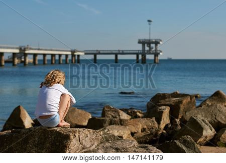 boy on the beach. he sits on the rocks. Bulgaria Burgas