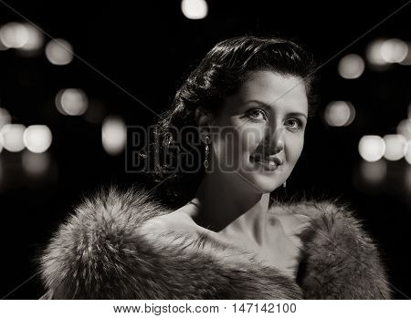woman studio portrait in hollywood style light with night lights background. black and white variation