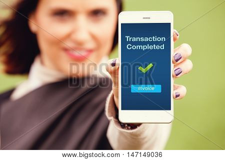 Mobile transaction notification. Woman holding a smart phone with Transaction completed message in the screen.