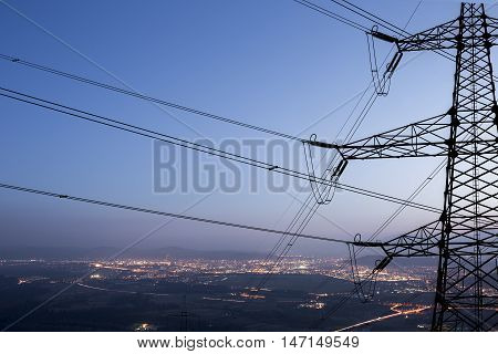 High power electricity transmission pylon silhouetted against the city.