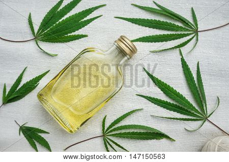 Leaves of cannabis and bottle of hemp oil on canvas. Hemp products. Agricultural technical culture