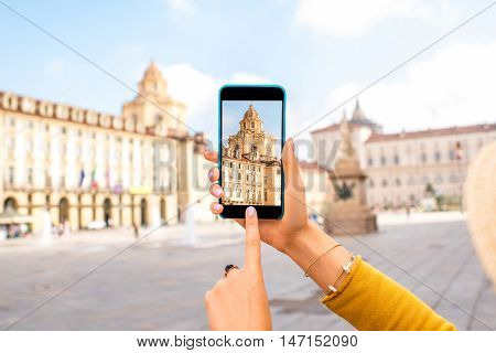 Holding a smart phone with photo of saint Lawrence church on the central square in Turin in Piedmont region in Italy