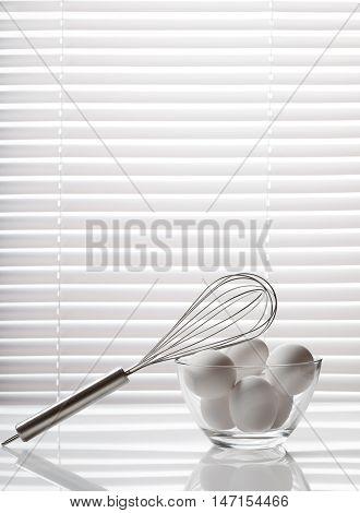 Whisk And Glass Bowl Full Of Eggs