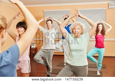 Senior woman doing balance exercise in yoga class at fitness studio