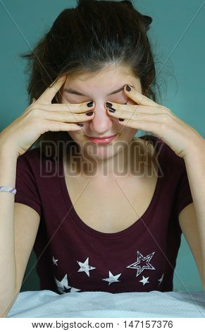 teen girl with tired eyes close up portrait on blue wall background