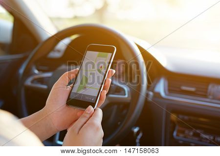 Woman In The Car And Holding Black Mobile Phone With Map Gps Navigation, Toned At Sunset.